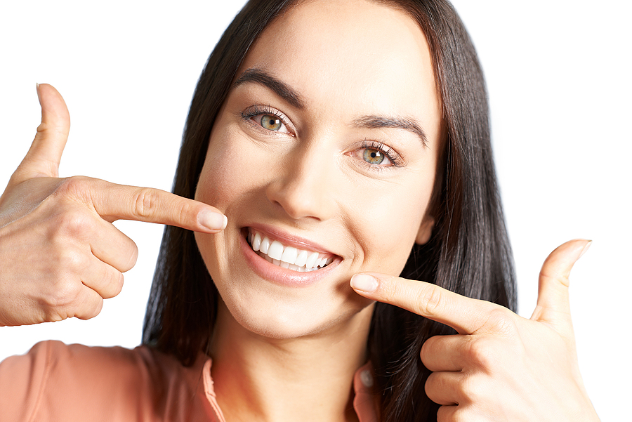 Woman Pointing To Her Smile With Perfect White Teeth