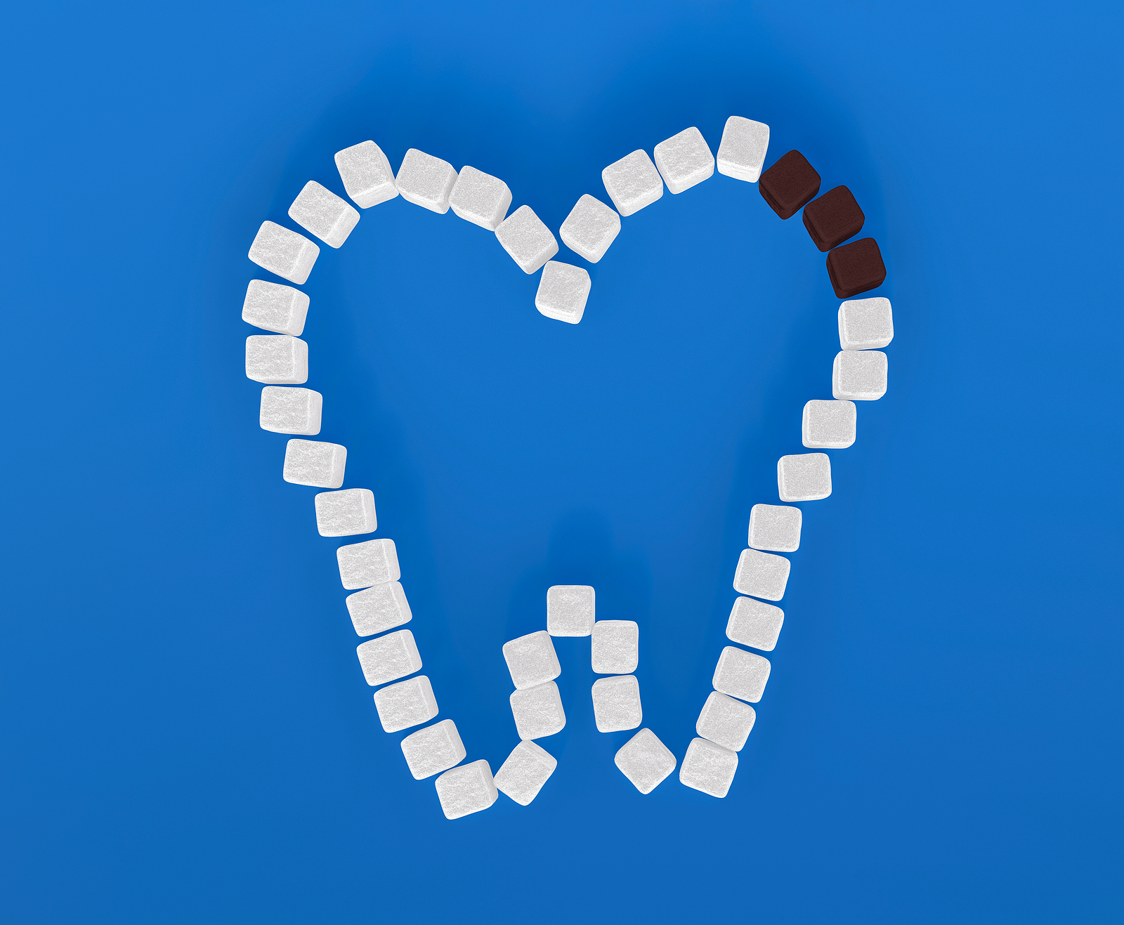 Tooth symbol created from white and brown sugar cubes showcasing decay tooth on blue background