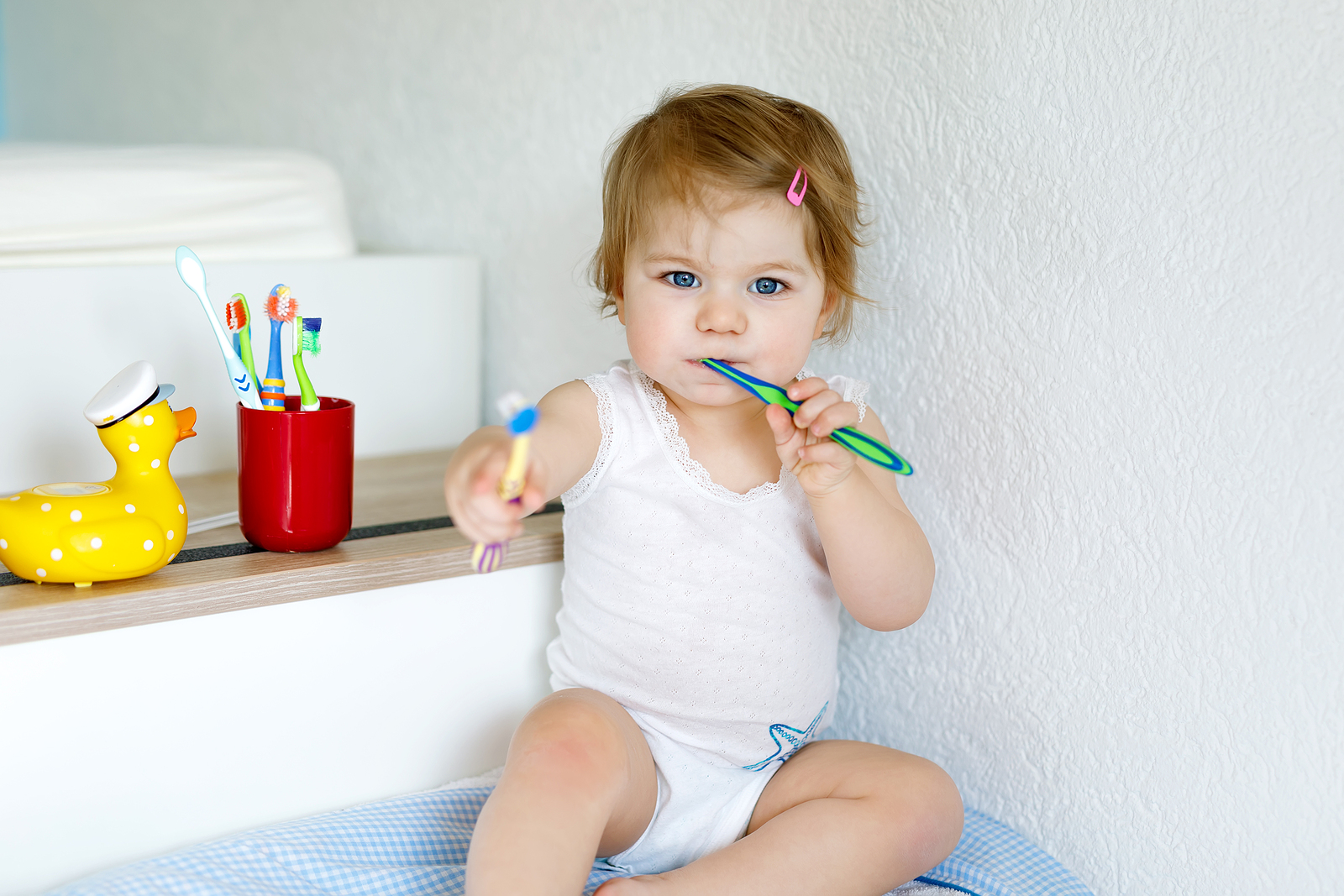Little baby girl holding toothbrush and brushing first teeth.